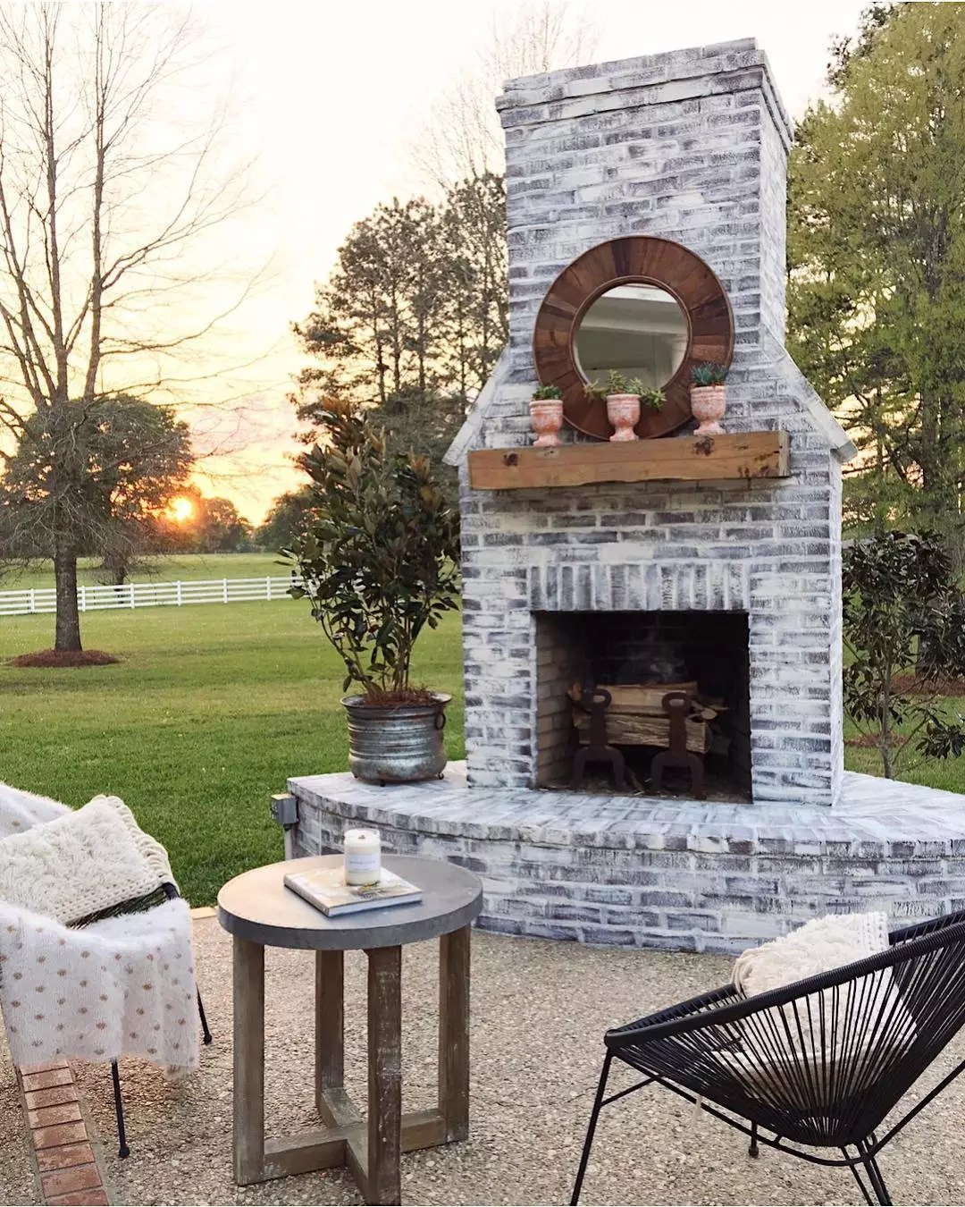 outdoor fireplace installed in the backyard with seating in front photo by Instagram user @cindimc.ivoryhomedesign