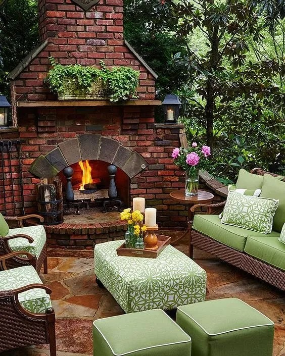 outdoor living room with green cushions and a fireplace lit photo by Instagram user @martinezvirginiaartist