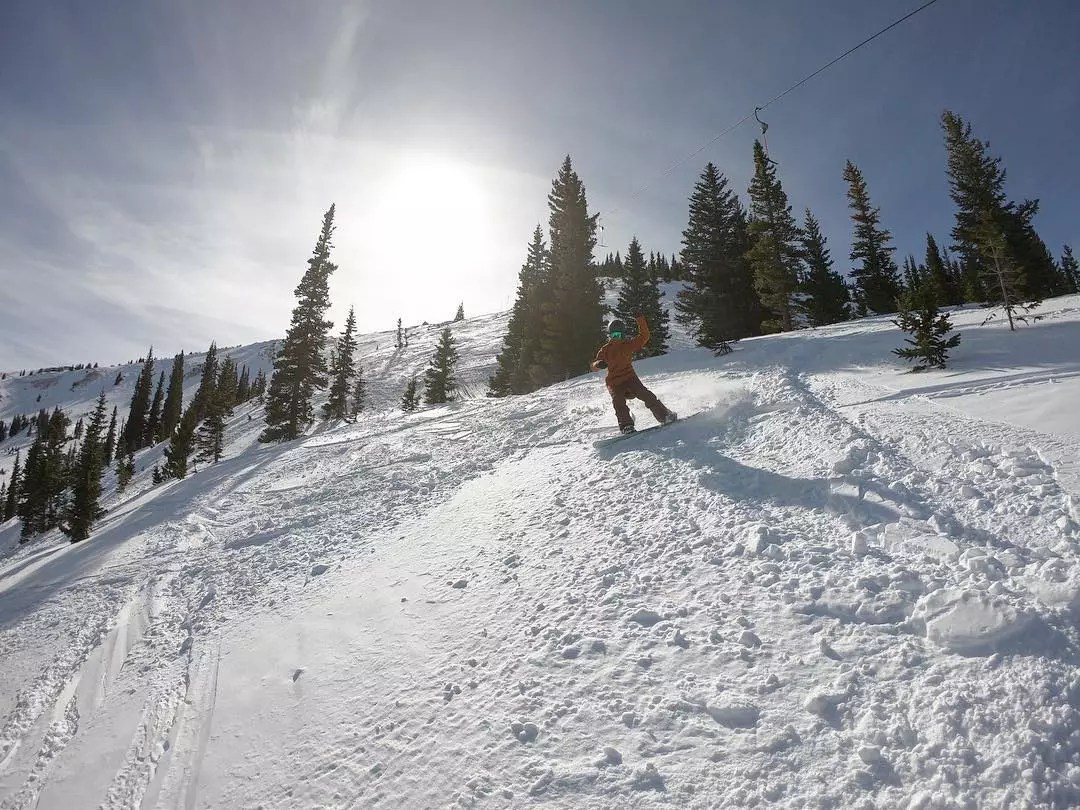 Person snowboarding down a snow-covered mountain Photo by Instagram user @breckenridgemtn