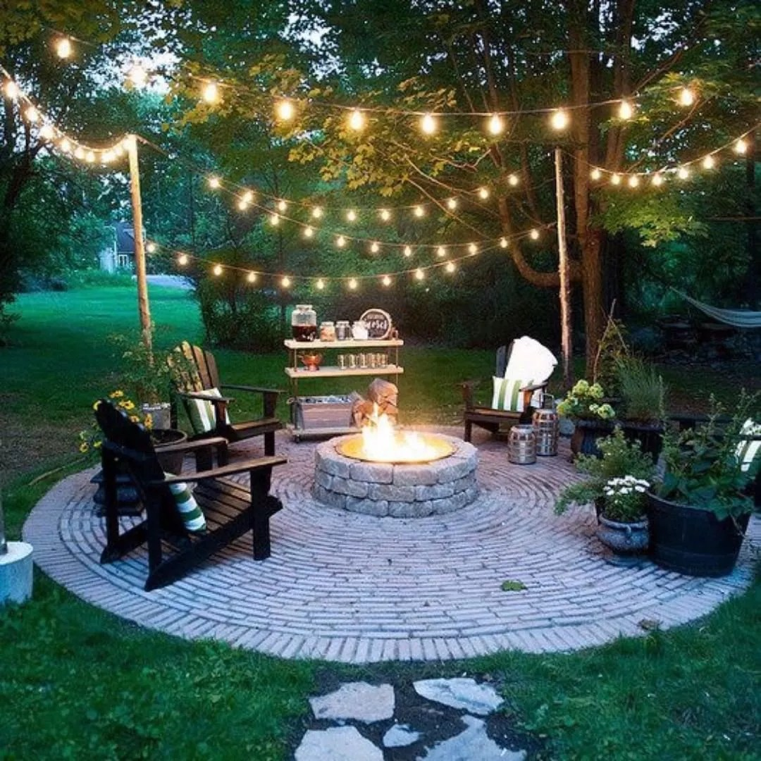 firepit set up with chairs surrounding on a brick patio with string lights overhead photo by Instagram user @mcgahacutler
