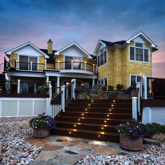 large house with deck steps that have lights installed into them photo by Instagram user @trexcompany
