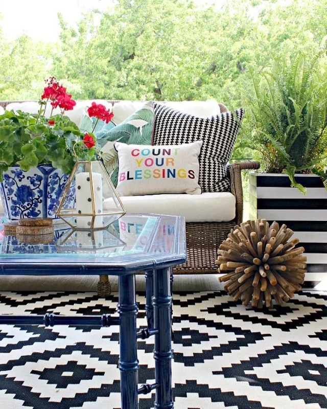 outdoor living space with couch and table with weatherproof rug photo by Instagram user @jenniferdimplesandtangles