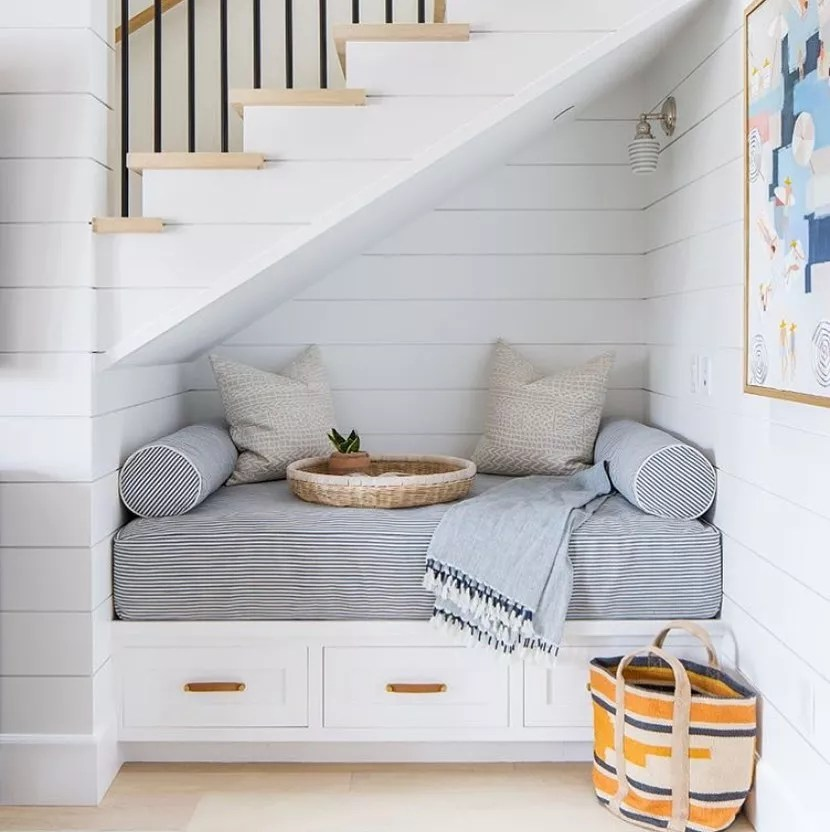 small nook under the stairs with pillows and bench pad photo by Instagram user @stretton.estates