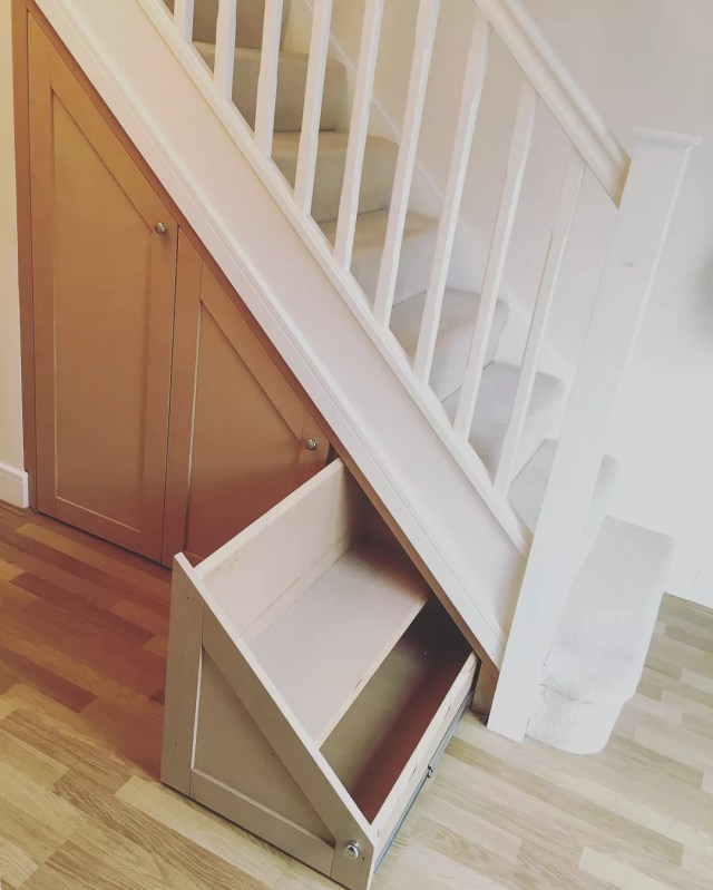 sliding drawer added beneath stairs in the home photo by Instagram user @fitted_furniture_team