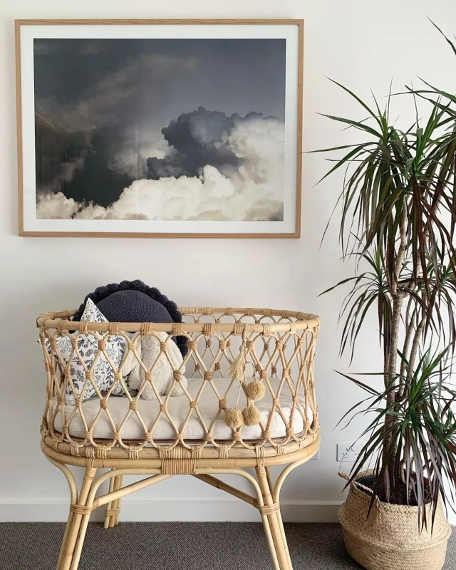 Bassinet under painting next to plant. Photo by Instagram user @derived_by_design