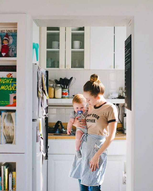 Woman Holding Her Baby Inside Her Apartment Kitchen in Brooklyn. Photo by Instagram user @hailey.marie.andresen