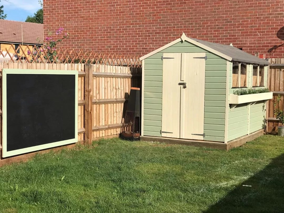 large chalkboard hung on the fence outside small garden shed photo by Instagram user @ourfirsthome54