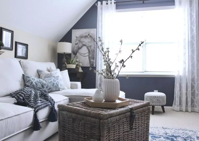 small room with white couch and wicker coffee table in middle of the room photo by Instagram user @citycottagechic