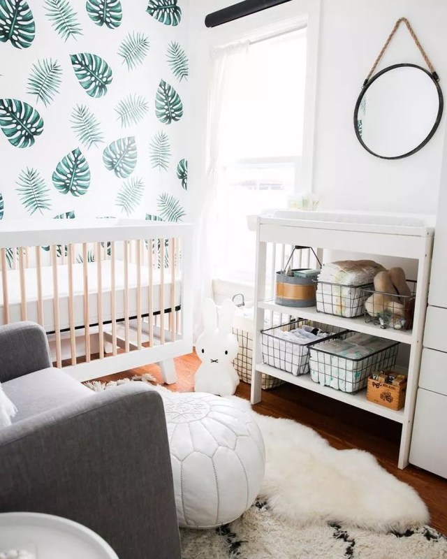 small nursery with white crib, leaves on the wall and small gray chair photo by Instagram user @babygrey_uk