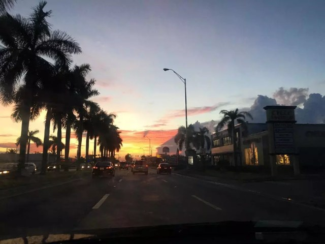 Looking down a street at sunset with palm trees on one side and buildings on the other. Photo by Instagram user @fitamazingcouple
