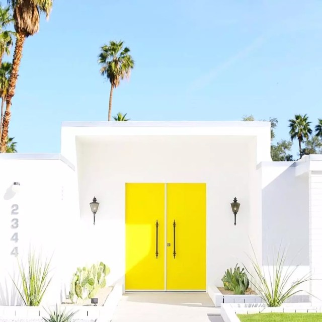 Bright yellow doors on modern house. Photo by Instagram user @goldenstrandjewelry