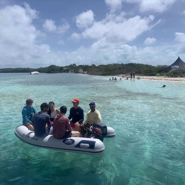 multiple people sitting on the sides of a dinghy in clear water photo by Instagram user @lamarboats