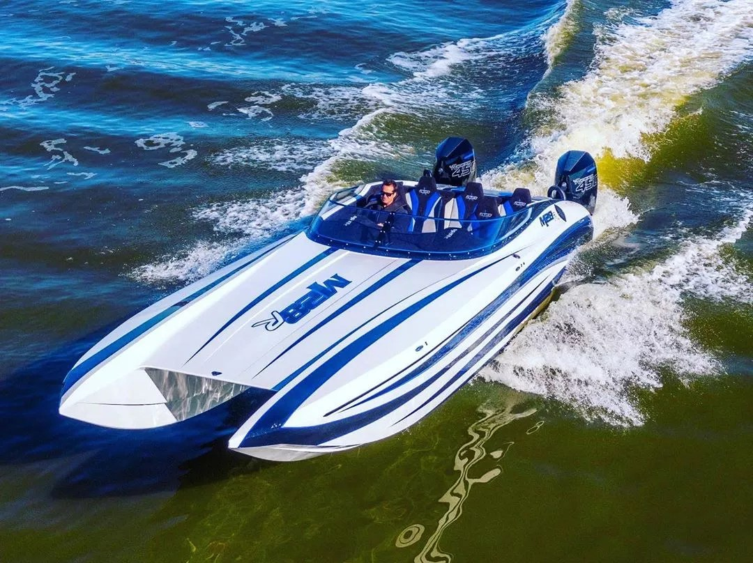 white and blue high performance boat driving in the water photo by Instagram user @andersonracingdcbm28