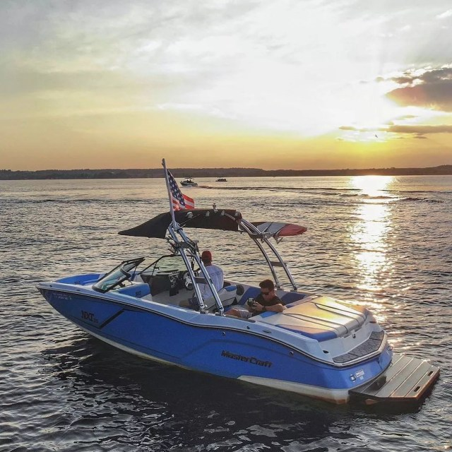 blue tow sports boat with American flag attached in the water at sunset photo by Instagram user @djdingz