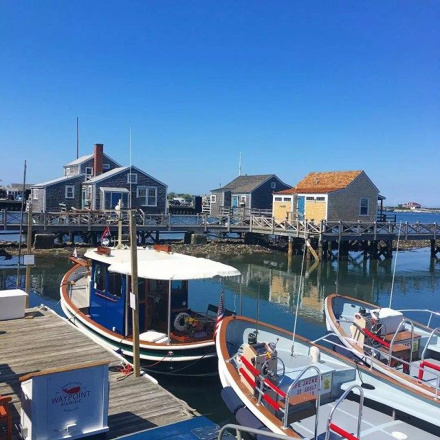 Boats on a Dock with Cottages in the Background at the Nantucket Boat Basin. Photo by Instagram user @thecottagesnantucket