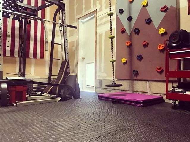 Home gym in garage with climbing wall and weight equipment. Photo by Instagram user @homegymaccess