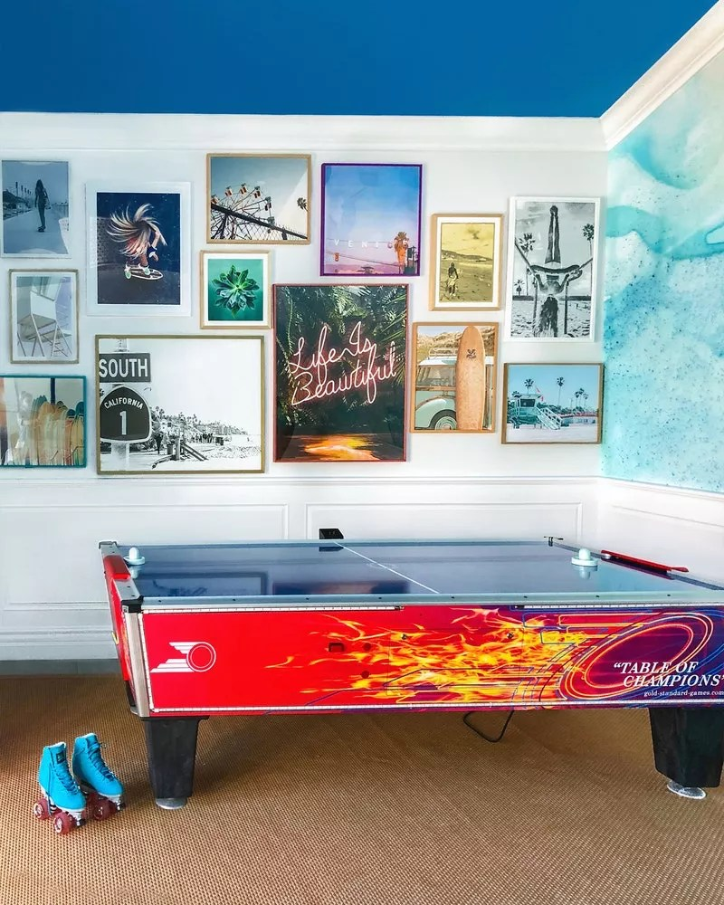 Room with air hockey table and framed pictures on wall. Photo by Instagram user @bennettlernerinteriors