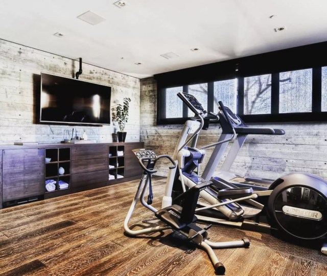 Home gym with flat screen TV and sound system in ceiling. Photo by Instagram user @dave_caplan_realtor