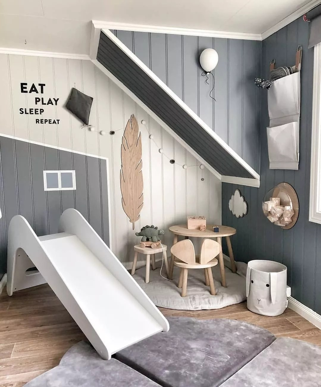 Grey kids room with fuzzy rug and white slide. Photo by Instagram user @jupiduu_original