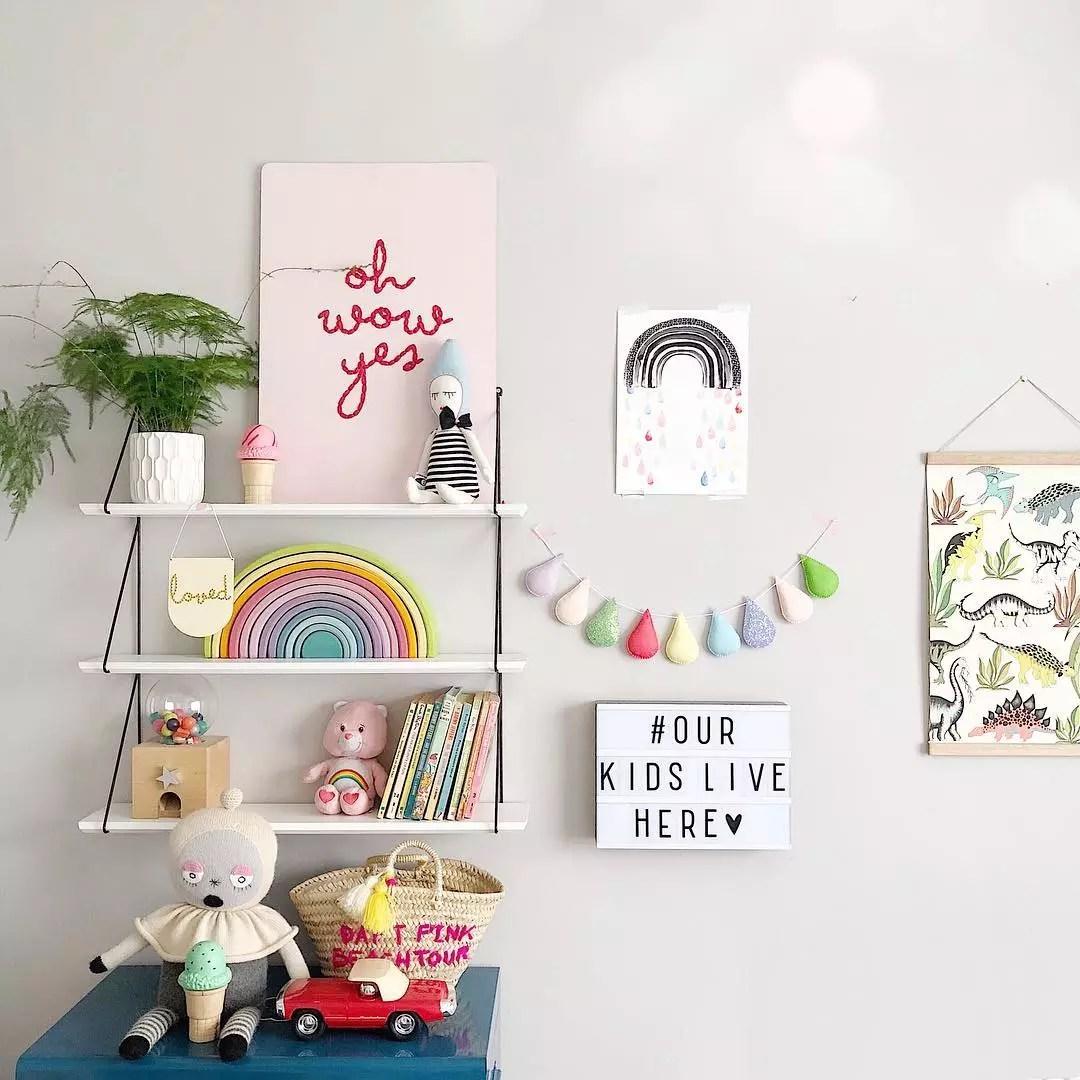 Floating shelves with rainbow decor on shelves. Photo by Instagram user @velveteen_babies