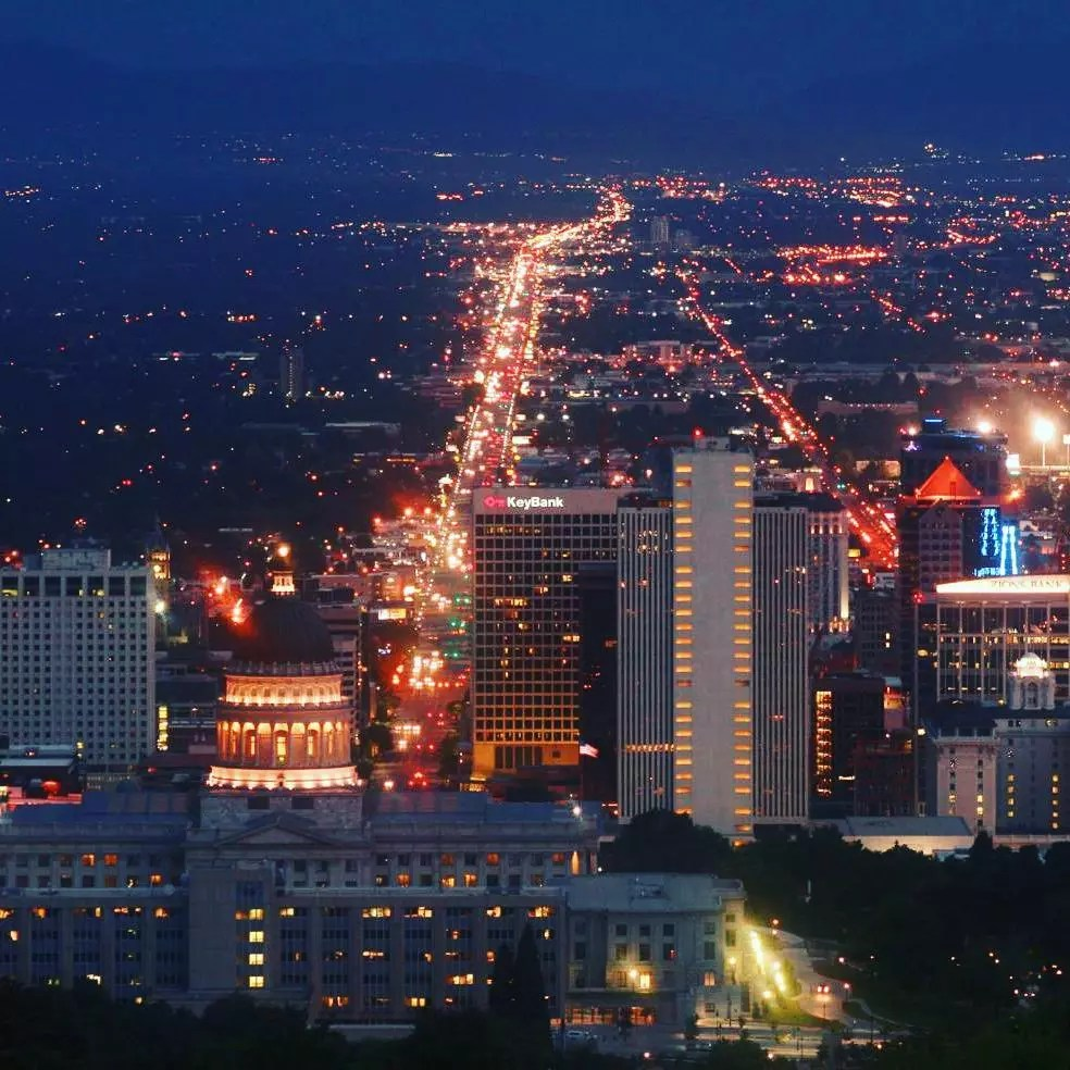 Aerial view of Salt Lake City skyline lit up at nighttime. Photo by Instagram user @daviesworldtravel