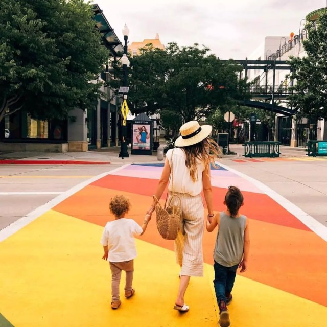 A woman and two young boys walk hand in hand across the street in a painted walkway. Photo by Instagram user @atthegateway