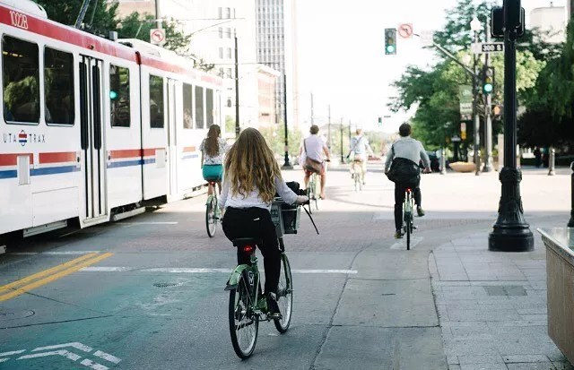 A woman, a man, and others bike through the street along side the rail train. Photo by Instagram user @slcbikeshare