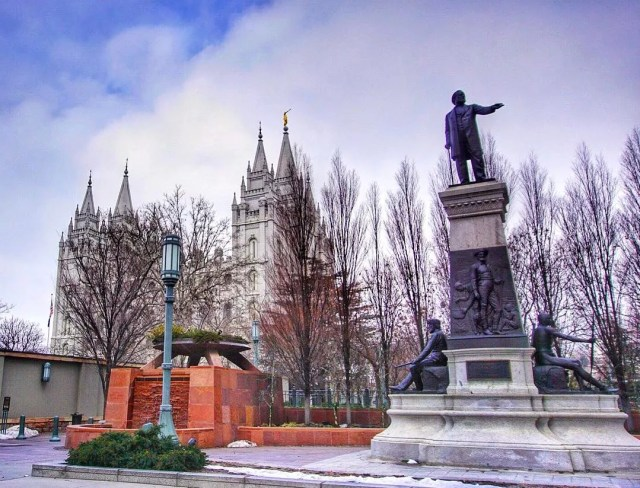 The Brigham Young Monument stands tall within a park at winter time with a view of the temple in the background. Photo by Instagram user @richardjv