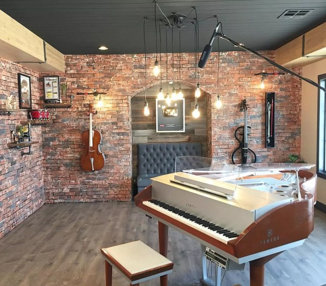 home recording studio with brick walls and piano in the middle of the room photo by Instagram user @tracibdesign