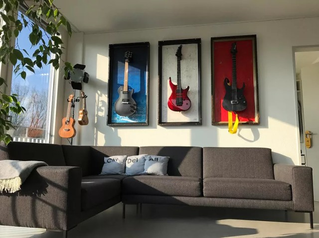 guitars placed in different colored frames as wall decor photo by Instagram user @gframes_guitardisplay