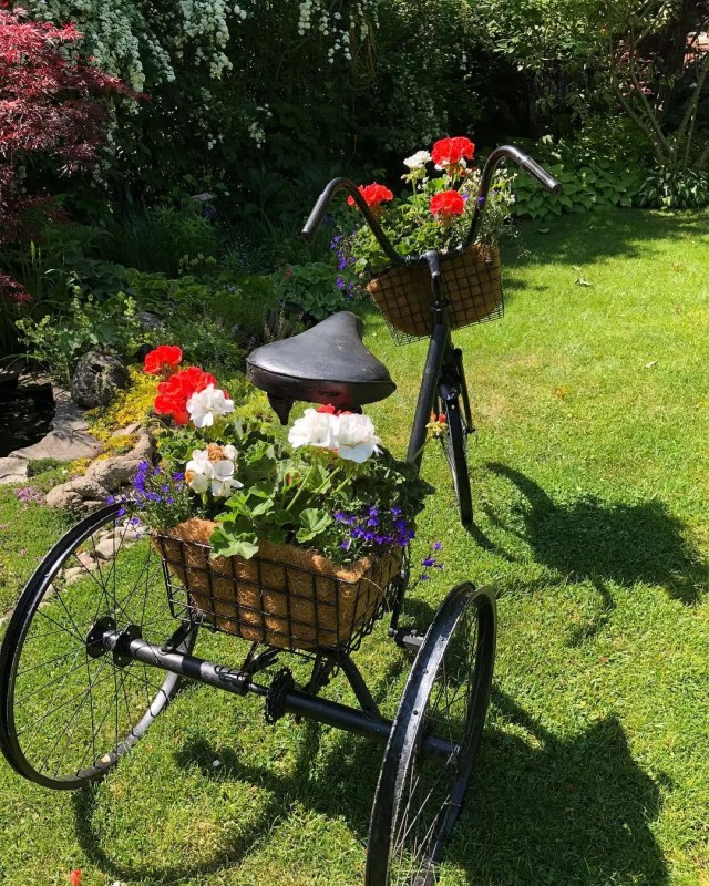 Bike with baskets of red flowers on them. Photo by Instagram user @cottage_inthecity
