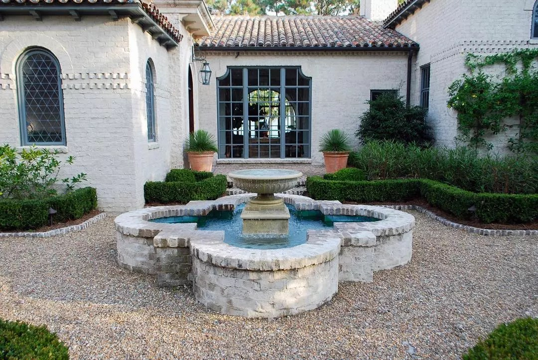 Giant white fountain in a home courtyard. Photo by Instagram user @alexsmithgardendesign