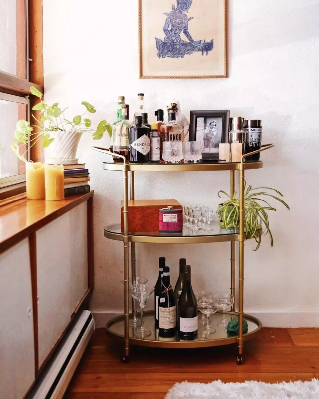 brass bar cart filled with liquor and nice glasses photo by Instagram user @venturetravelist