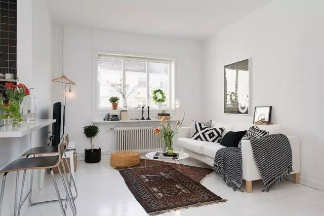 small apartment with statement pieces like white couch and small rugs photo by Instagram user @studio_apartment