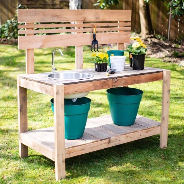 Wooden potting bench with blue pots on it. Photo by Instagram user @the.handymans.daughter