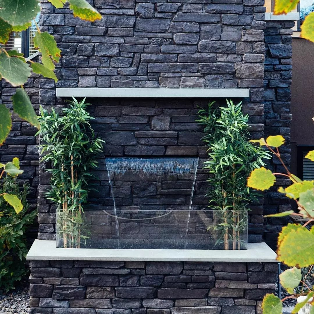 Water blade fountain on gray stone wall. Photo by Instagram user @waterbydesign