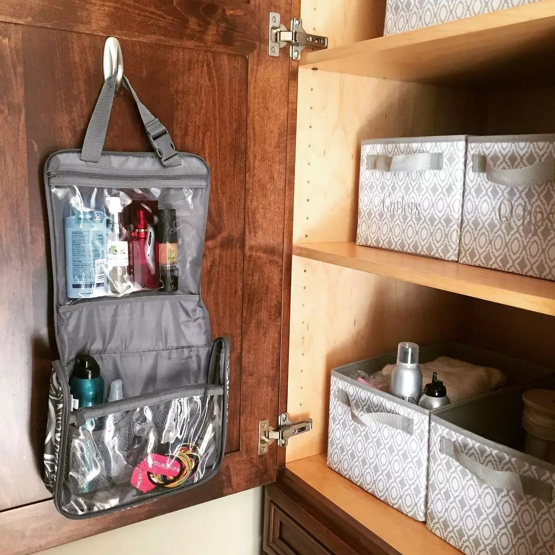 Toiletry bag hanging on command hook in cabinet interior. Photo by Instagram user @tiffanyshearobinson