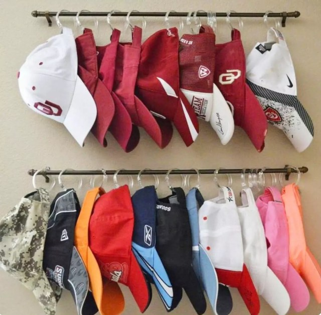 Baseball hats on shower curtain rings and metal rod. Photo by Instagram user @thingsinorder