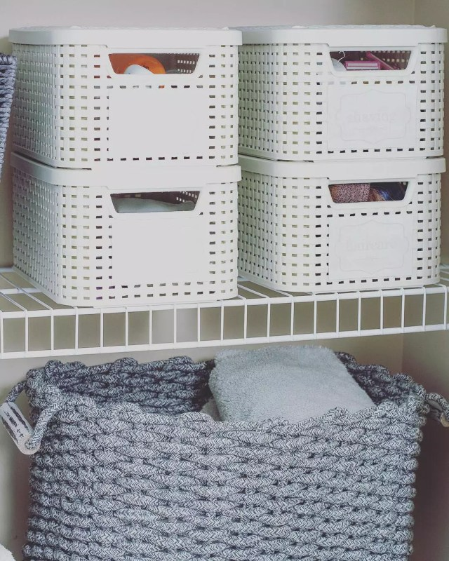 Plastic organizer totes on wire closet shelving. Photo by Instagram user @straightened_spaces