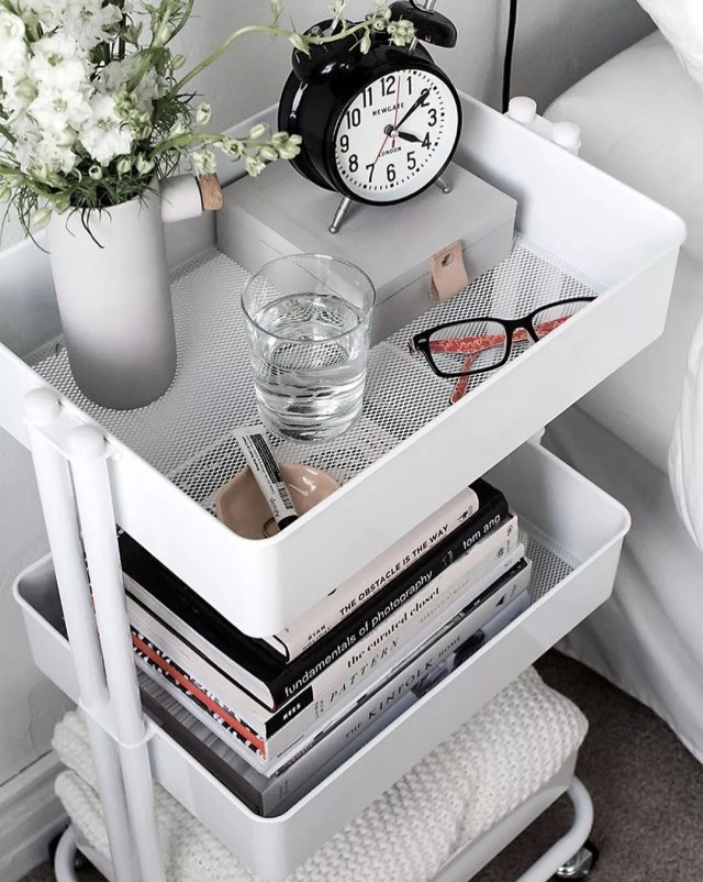 White rolling storage cart filled with decor next to bed. Photo by Instagram user @housejunkie_
