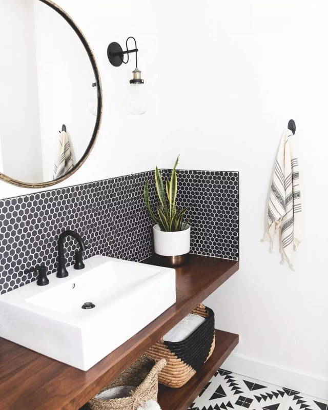 black tile backsplash with white sink and wooden counter in bathroom photo by Instagram user @theresidencybureau