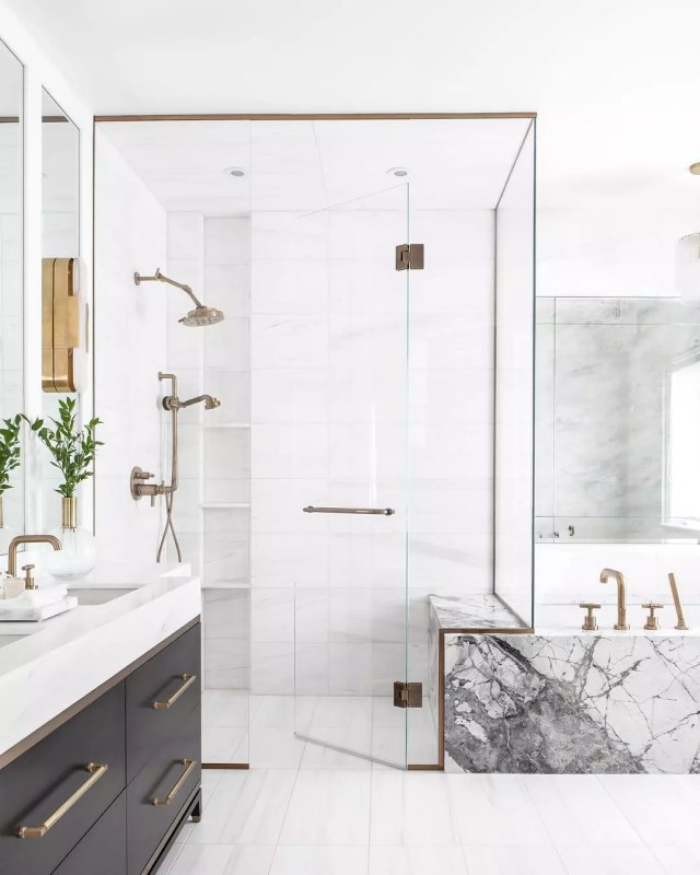 bathroom with white tile, glass shower walls, and gold hardware photo by Instagram user @kielyramosphoto
