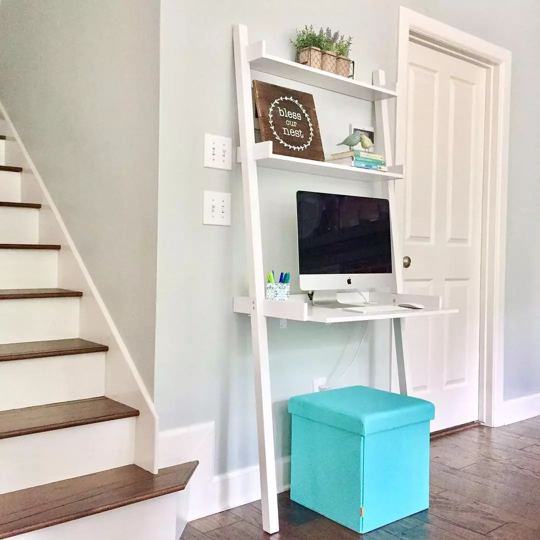 Wall desk with laptop and seating cube. Photo by Instagram user @onehappyhousewife