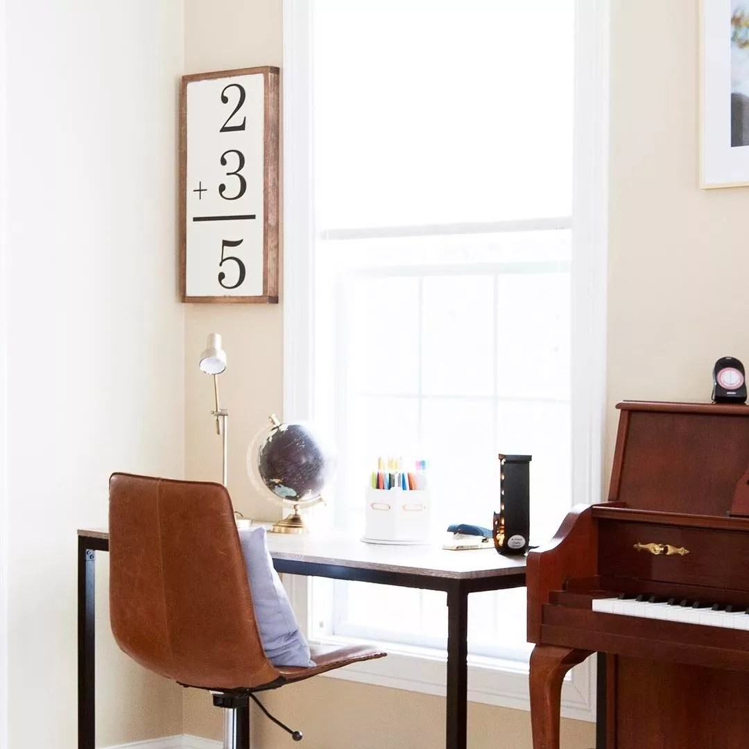 Kids study area set up in room with piano. Photo by Instagram user @ordinatoathome