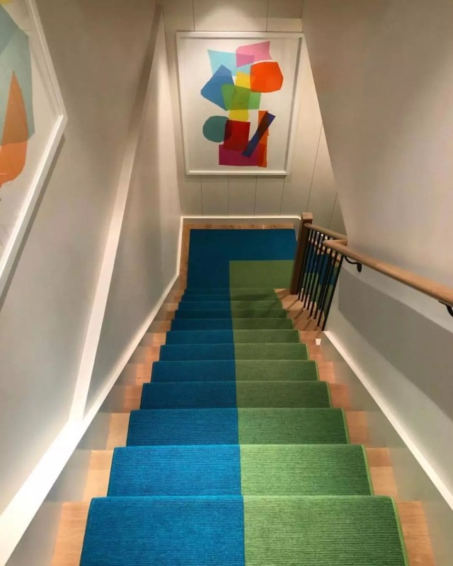 colorful basement stairwell with art on the walls and green and blue carpet photo by Instagram user @melaniemorrisinteriors