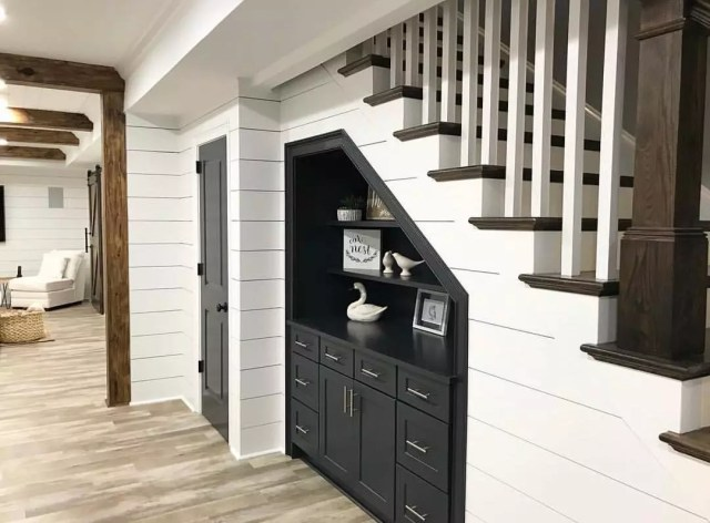 small storage space under stairs in basement with shiplap on the wall photo by Instagram user @linenandbasil