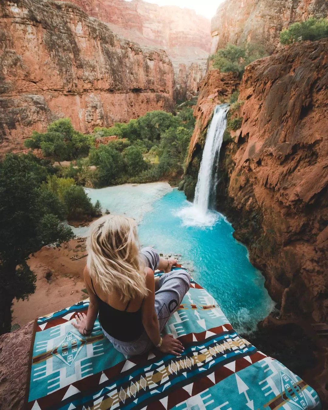 Woman sitting on cliff in Havasupai. Photo by Instagram user @braybraywoowoo
