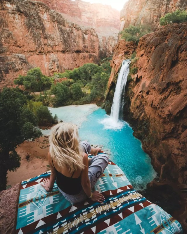 Woman sitting on cliff in Havasupai. Photo by Instagram user @braybraywoowoo