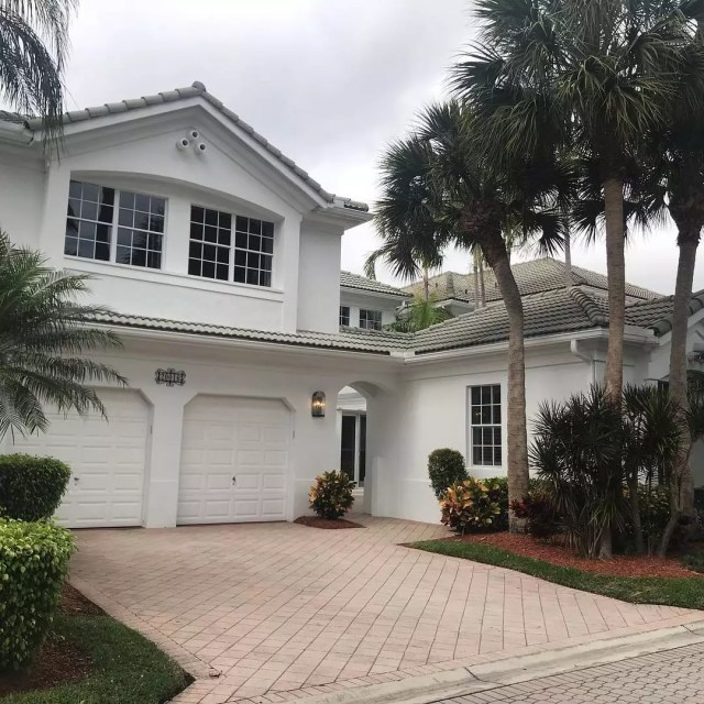 Two story white home with gray roof and 2 car garage. Photo by Instagram user @mssellsparadisemiami