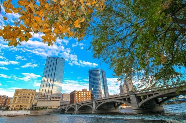 Grand Rapids skyline on the river with fall color tree leaves photo by Instagram user @experiencegrandrapids